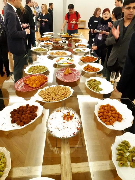 Pitkä lasipöytä, jonka päällä on tarjolla lukemattomia lautasellisia cocktail-naposteltavaa. Konferenssivieraat ovat kerääntyneet pöydän ympärille keskustelemaan.