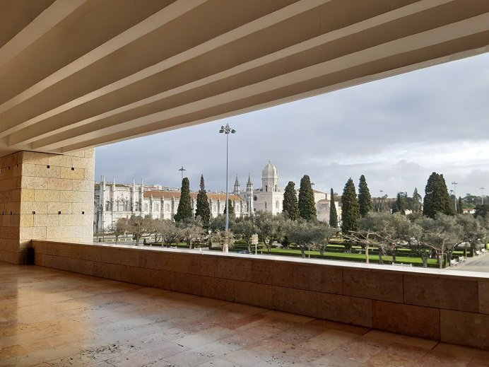 Pitkä, valkoiseksi rapattu, punakattoinen luostari, jossa on yksi kahdeksankulmainen korkea torni näkyy korkeiden sypressien takaa kuvan taustalla.