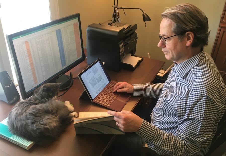 Aikuiskasvatus-lehden metadataa voidaan luoda myös etätyössä. Esko Clarke Sario kotityöpisteellä, edessään näytöillä laaja Excel-taulukko ja skannattu tiedosto. Kissa makaa työpöydällä seurana.