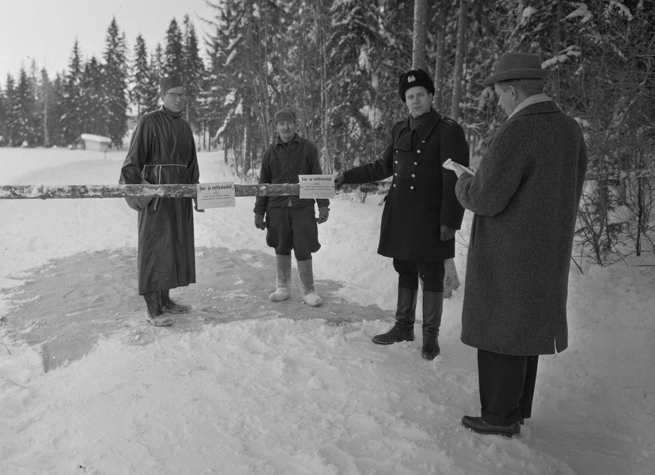 Miehiä portin edessä ja takana. takana olevilla suoja-asut