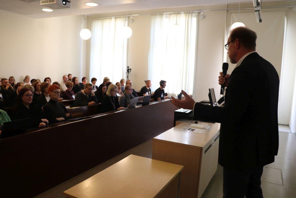 Pekka Olsbo puhuu luentosalin edessä.