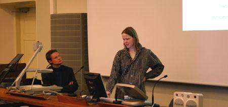 Kalle Korhonen istuu, Rita Voigt pitää esitystä.