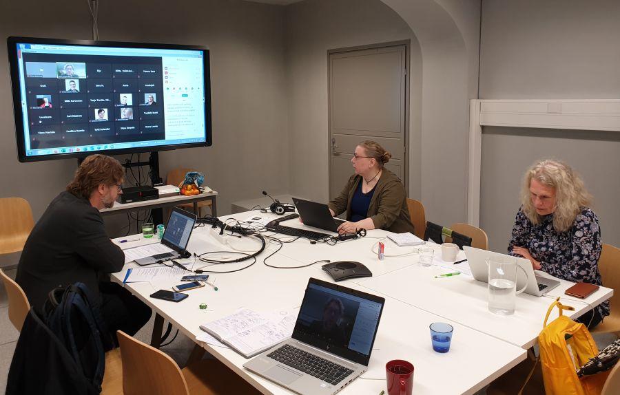 Tilaisuuden järjestäjät istuvat pöydän ympärillä kannettavien tietokoneiden ääressä